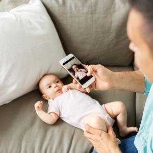 En man tar en bild med sin telefon på ett spädbarn som ligger i soffan.