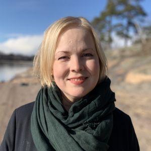 Närbild av en blond kvinna som står på en klippig strand i solskenet.