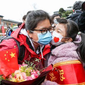 En hälsovårdare som jobbat i Wuhan välkomnas av sin dotter efter att ha återvänt hem