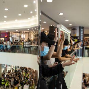 Mielenosoittajat viittovat katsojille ostoskeskuksessa järjestetyssä protestissa 10. toukokuuta 2020.