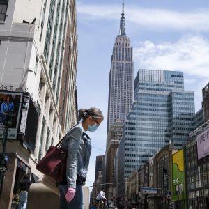Nainen kävelee maski naamallaan New Yorkissa.