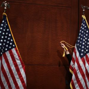 Två amerikanska flaggor. Bakom den ena flaggan rättar en hand till banden.