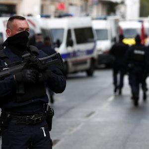Svartklädd och maskerad polis håller i en automatkarbin