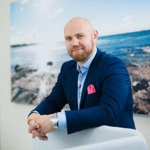 Aki Eriksson klädd i mörkblå kavaj står i ett kontor framför en stor väggplansch med klippor och hav.