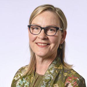 En kvinna med axellångt blondt hår ser in i kameran och ler. Bakgrunden är vit, hon har glasögon med mörka bågar på sig och en görnblommig skjorta som syns vid axlarna.