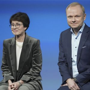 Sari Baldauf iklädd en grå kavaj bredvid Pekka Lundmark iklädd en blå kavaj. Halvkroppsbild.