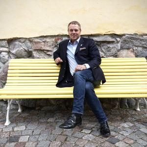 Jan Vapaavuori istuu penkillä Helsingin kaupungintalon sisäpihalla.