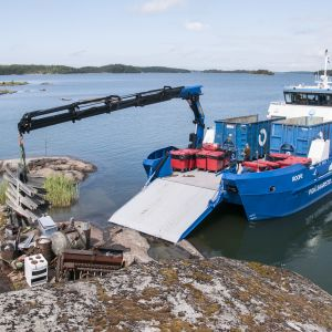 Servicefartyget Roope lyfter ombord metallavfall i skärgården