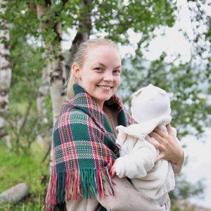 Miisa Nuorgam katsoo kameraan vauva sylissään, taustalla näkyy lehtevien koivunoksien läpi jokimaisema.