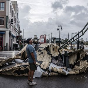 En man står i ett gathörn och tittar på en orkanskadad byggnad.