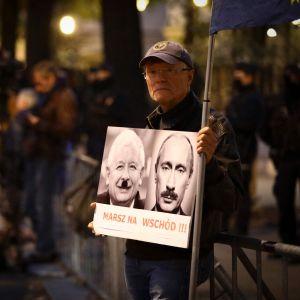 Puolan korkeimman oikeuden edustalle kokoontui torstai-iltana joukko mielenosoittajia. Mies piti kädessään kylttiä, jossa Venäjän presidentti Vladimir Putin ja valtapuolue PiSin johtaja Jaroslaw Kaczynski esiettiin diktaattoreina.