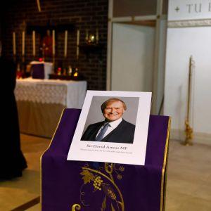En bild av David Amess uppställd i en kyrka. En präst med munskydd syn i bakgrunden.