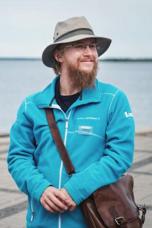 Toni Junes står framför inre hamnen i Kemi med en hatt på huvudet, leende bakom sitt tomteskägg.