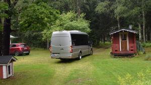 En silverfärgad minibuss på en gårdsplan. Sommar.