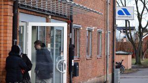 En person går in genom dörren till Arbetsförmedlingens kontor.