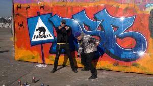 Lasse grönroos och theo sandström framför graffitivägg