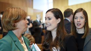 Anna-Maja Henriksson och Sanna marin talar med varandra. I bakgrunden syns Li Andersson, i förgrunden en suddig Katri Kulmuni.