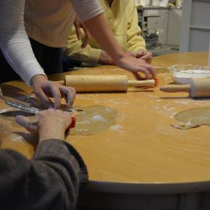 Närvårdare hjälper äldre att baka pepparkakor på äldreboendet Carl & Carolina i Vasa