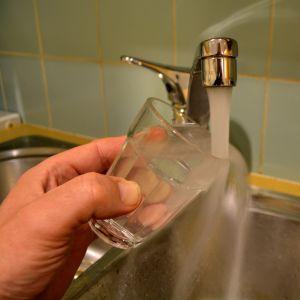 vatten som rinner från kran till dricksglas