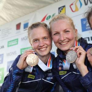 Sari Anttonen och Marika Teini visar upp sina medaljer