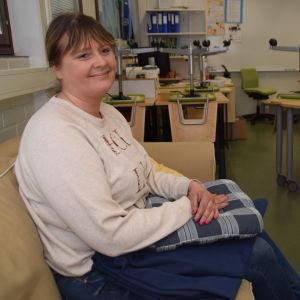 En kvinna sitter på en soffa i ett klassrum. Hon heter Anu Hausen och är rektor för Päivärinteen koulu i Sjundeå.