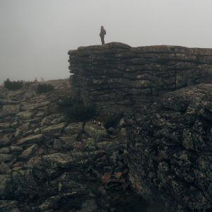 Mies seisoo kivimuodostelman päällä harmaassa kalliomaisemassa
