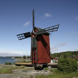 Vy över ön Gullkrona. Man ser väderkvarnen och segelbåtar i besökshamnen.