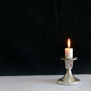 Kort, vitt stearinljus brinner i en liten ljusstake.