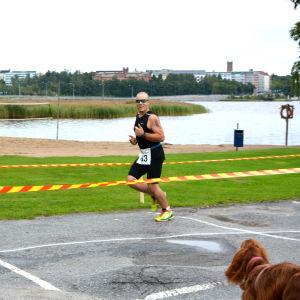 Triathlet springer längs strandkanten i Vasa sun city triathlon