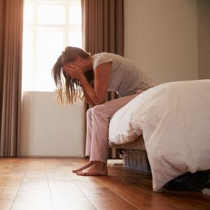 Kvinna sitter i en säng med ansiktet i sina händer.