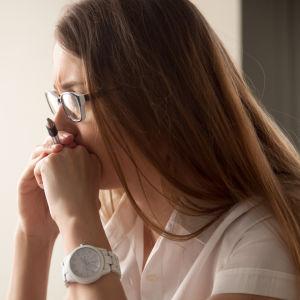 Kvinna i glasögon ser stressad.