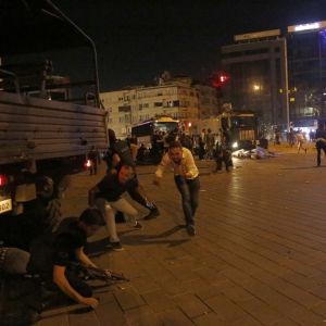 Människor tar skydd vid Taksimtorget i Istanbul.