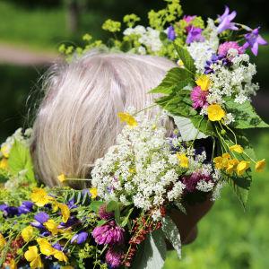 Leena Toivonen niityllä kukkaseppele päässään.