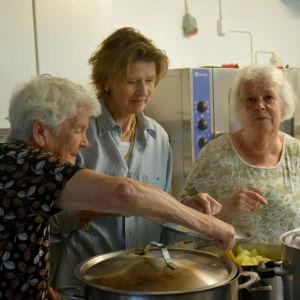 Ella Engberg, Loa Droz och Else-Maj Bäckström står i ett kök och rör i en kastrull med potatis.