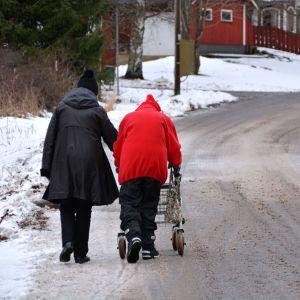 Två kvinnor går längs en väg med en rullator.