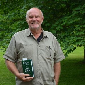 Bror West står med en vinguide i handen i en lummig, grön miljö.