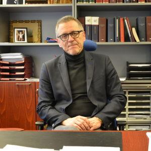 Daniel Allén sitter på sin stol på sitt kontor bakom ett stort skrivbord. På hyllorna bakom honom finns många mappar.