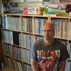 Jan Richardsson sitter framför sina skivhyllor.