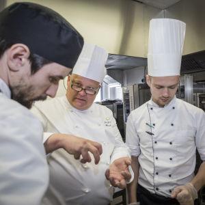 Kocken Mikael Eskman förklarar någo för två andra kockar.