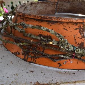 Kvistar fästa med metalltråd på en tudelad grindkrans