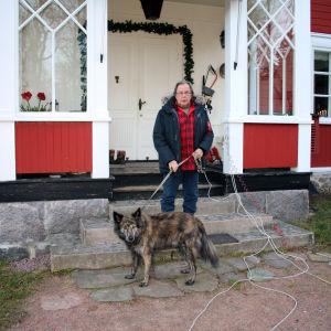 Cay Karlsson framför huset i Bromarf med hunden Nasti