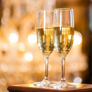 Två glas fyllda med mousserande vin står på ett bord.