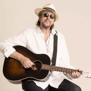 Heikki Harma, a.k.a. Hector sitter med en gitarr i famnen.