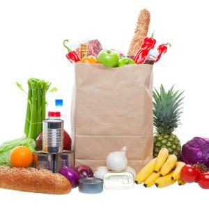 En brun papperskasse med olika matvaror, fotograferad från sidan.