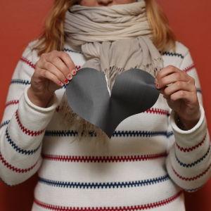 Flicka river ett pappershjärta i två