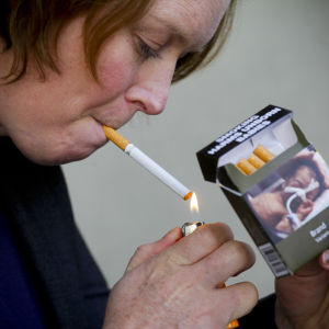 En kvinna tänder en tobak.