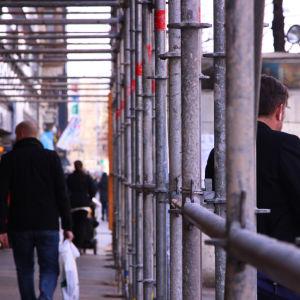 Människor vandrar under byggställningar.