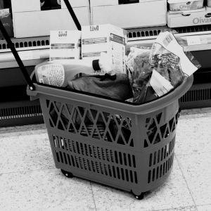 Köpkorg fylld med varor på affärsgolv