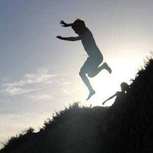 Lapsi hyppää kukkulalta