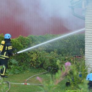 Brandman släcker elden vid Magasingatan i Ekenäs.